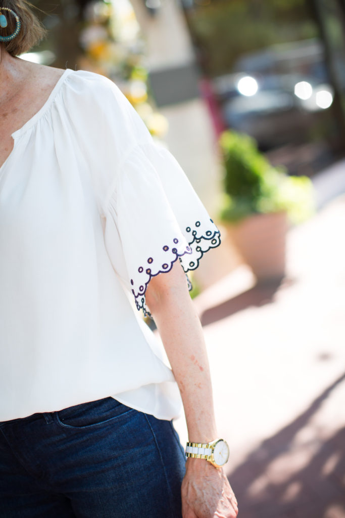 Ann Taylor has white blouses with embroidery which is a fashion trend for over 40 style.