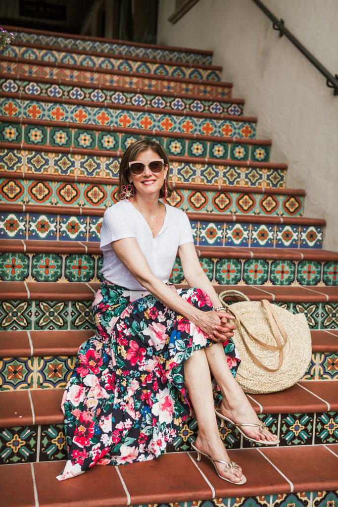 Vacay mode for Dallas Blogger with dark floral skirt and straw bag.