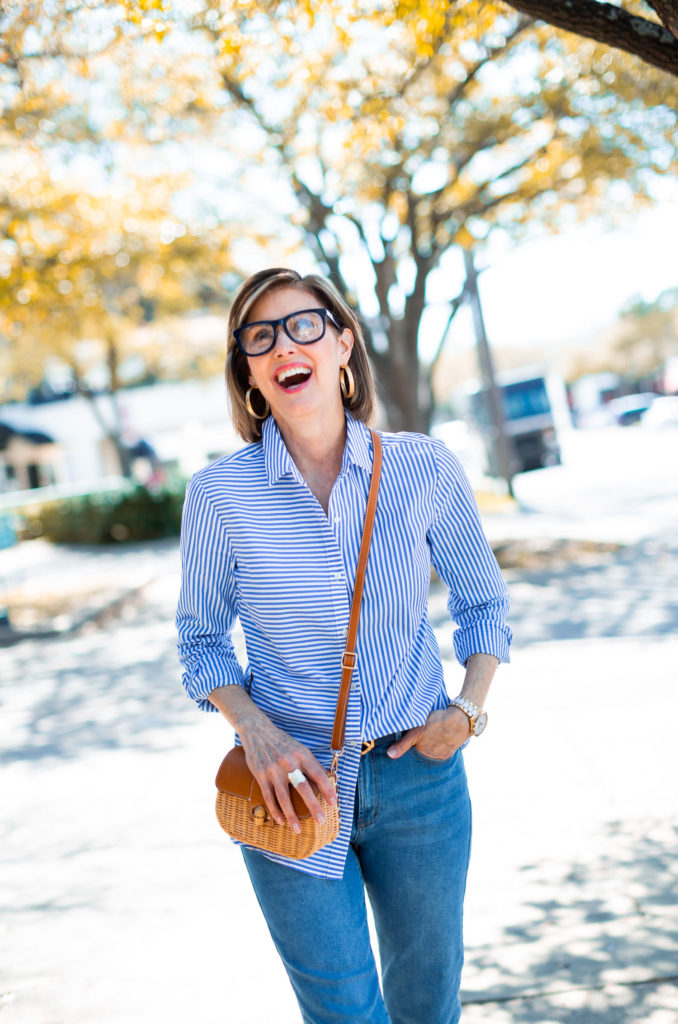 Over 50 blogger in stripe shirt with straw cross body bag.